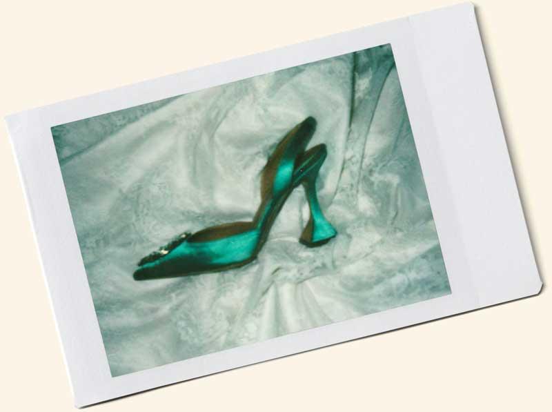 Polaroid of an emerald Amina Muaddi shoe