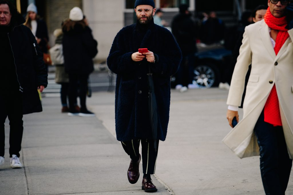 A Photo of a Stylish Man in a Teddy Coat and Wooly Hat Walking Down the Street