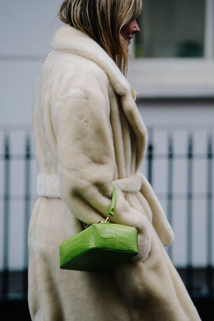 An Image of a Woman Wearing a Cream Fur Coat and a Green Rejina Pyo Bag
