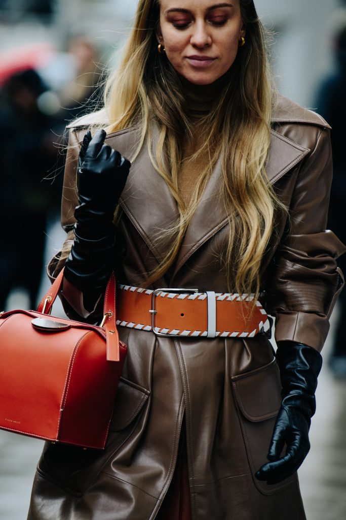 An Image of a Woman Wearing a Brown Leather Coat and Orange Belt
