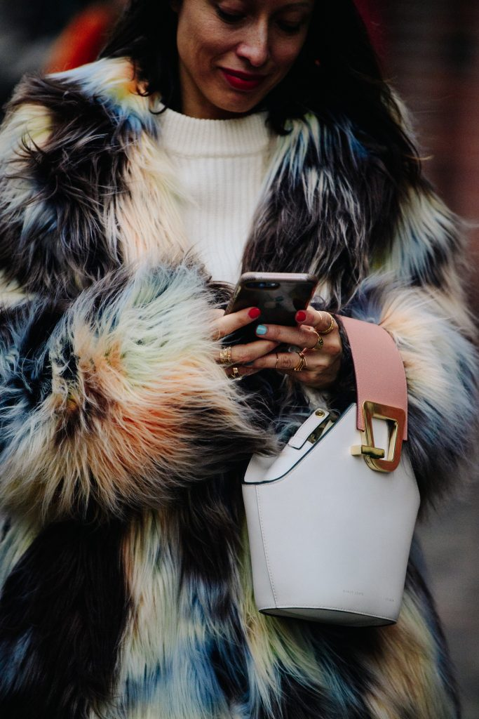 An Image of a Woman Wearing a Tie Dye Coat With a Danse Lente Bag During Fashion Week