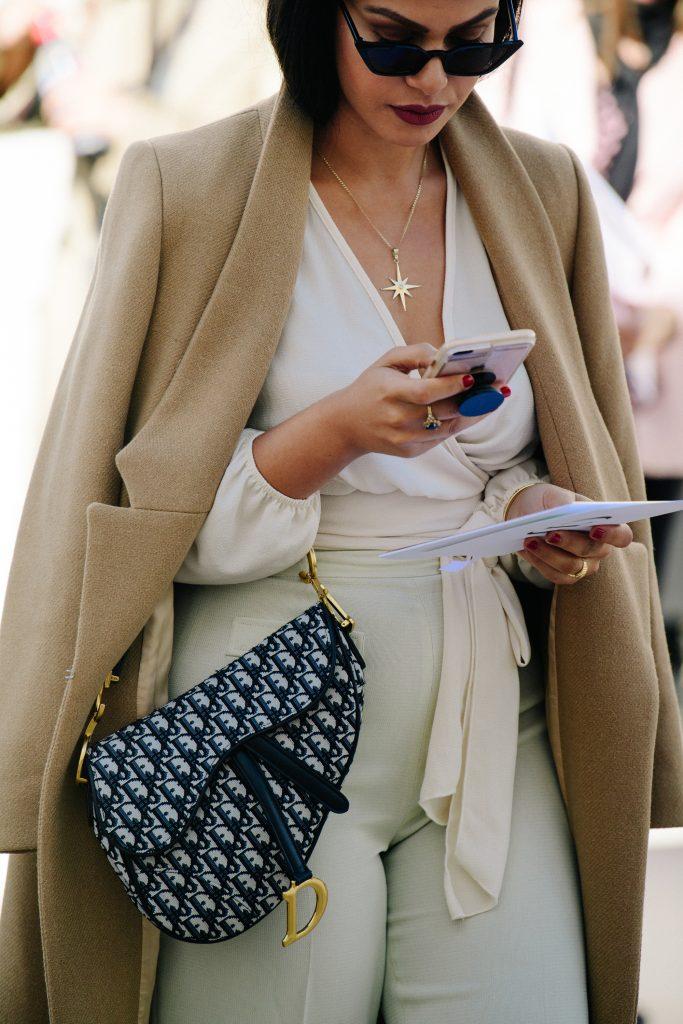 An Image of a Woman Carrying a Dior Saddle Bag